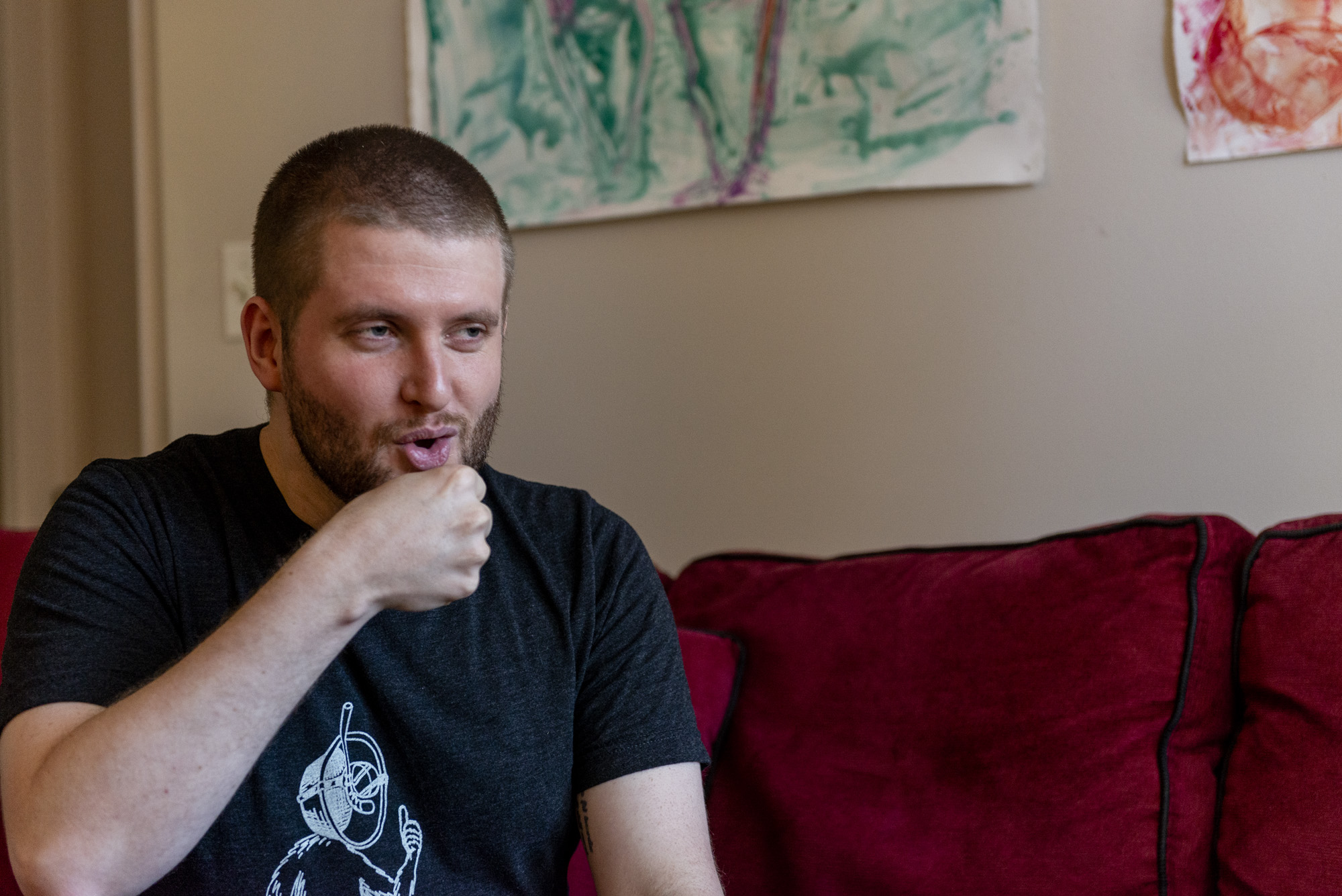 Image: The subject is in full focus. The red couch is in view behind them and the lower half of a few paintings on the wall which are green and orange/red. The artist is clearly re-enacting a blowjob here with his mouth being half closed and his hand in a fist and close to his mouth. Photo by Ryan Edmund Thiel