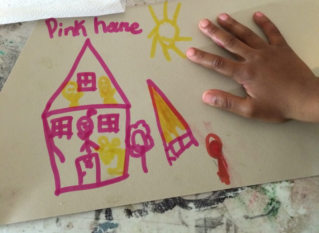 """Image: A drawing at Pink House, St. Louis, held down by a child's hand. The drawing is bright pink and yellow on white paper. The drawing shows a cross-section of the house with people inside on the first and second floors; outside the pink house are the words """"Pink house,"""" a sun, trees, and more. Photo by Patrick Fuller. Courtesy of the artist."""
