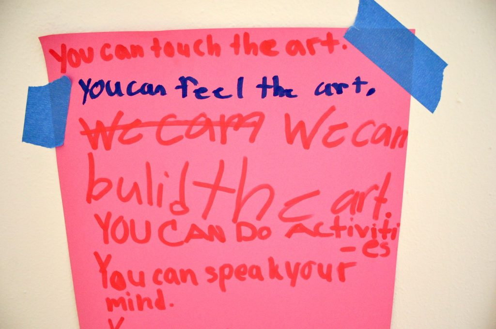 """Image: A sign at Pink House, St. Louis. The sign is bright pink and reads, in red and blue marker, in a child's handwriting: """"You can touch the art. You can feel the art. We cam We can build the art. You can do activities. You can speak your mind."""" The sign is attached to a white surface using blue tape. Photo by Patrick Fuller. Courtesy of the artist."""