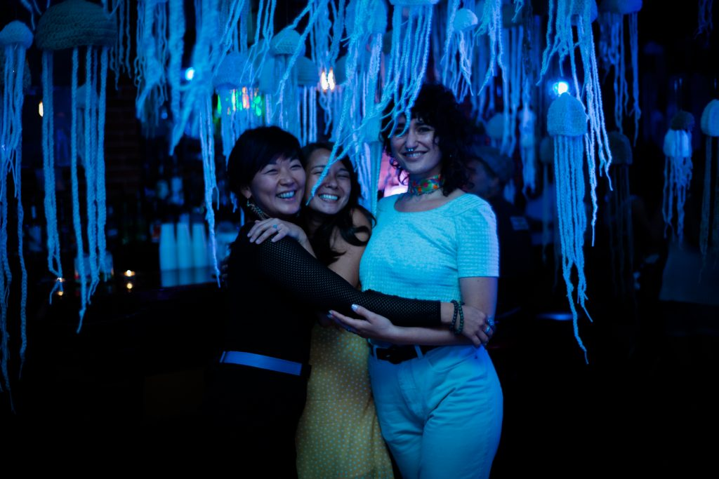 """Image: Regina Martinez at """"the clothesline"""" in St. Louis in 2019. Martinez (right) poses with co-founders April Fulstone and Angelina Fasano. They stand together, smiling at the camera with arms around each other, in a dark space lit by bluish light. Hanging from the ceiling and all around them are dozens of crocheted jellyfish made of light-colored yarn. Fulstone wears all black with a blue belt, Fasano wears a yellow and white patterned outfit, and Martinez wears a light top and light pants with a bright, multi-colored choker. Photo by Carly Faye. Courtesy of the artist."""