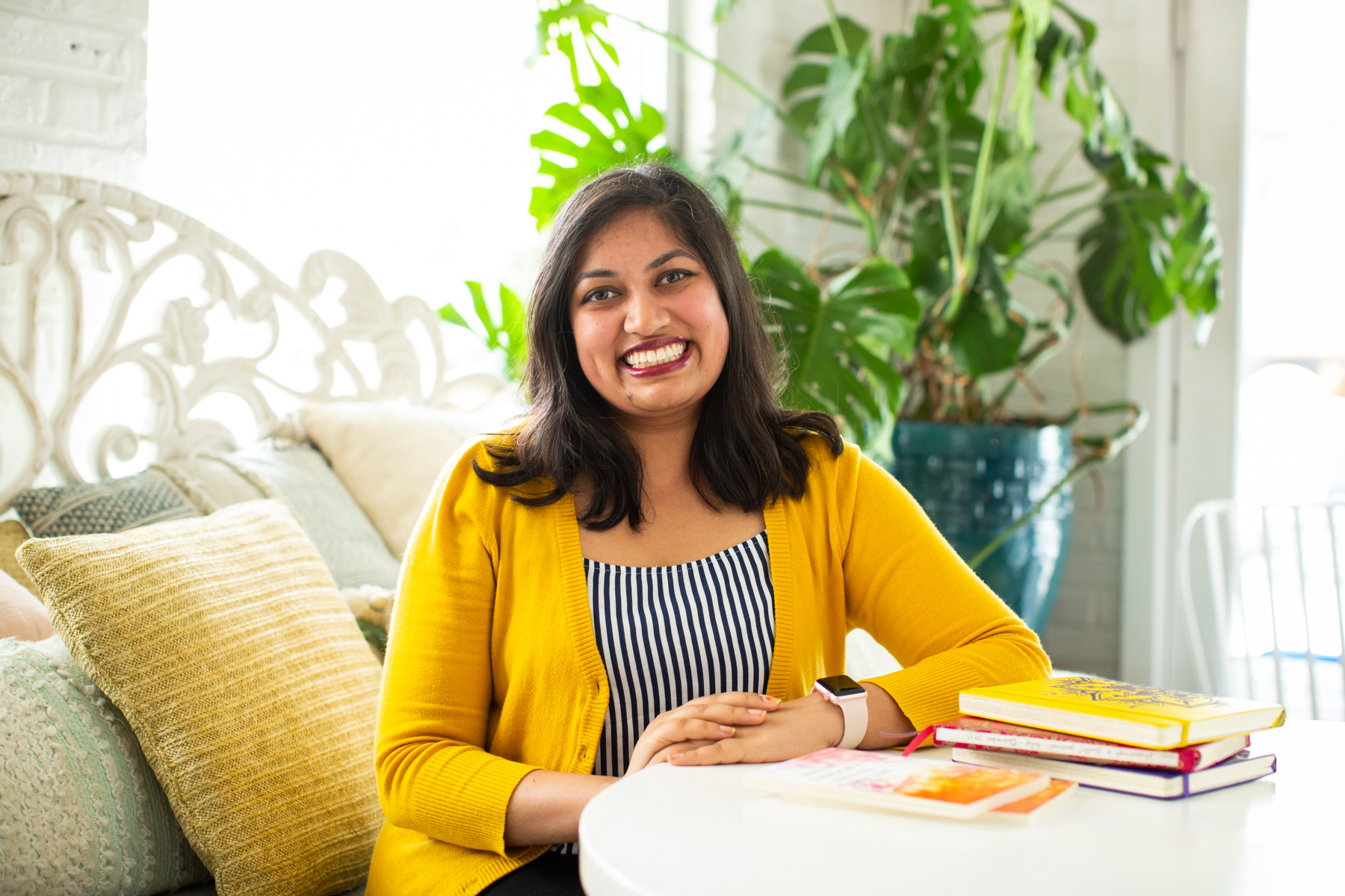 "Featured image: Sharanya Sharma. Sharma sits with hands folded on a white table, with copies of ""Set Fire to This Crooked House"" and multi-colored notebooks in the foreground. Sharma wears a marigold cardigan open over a black and white striped shirt and smiles at the camera. Behind Sharma are several pastel throw pillows and a large plant, and natural light comes through the windows. Photo by Kristie Kahns Photography."