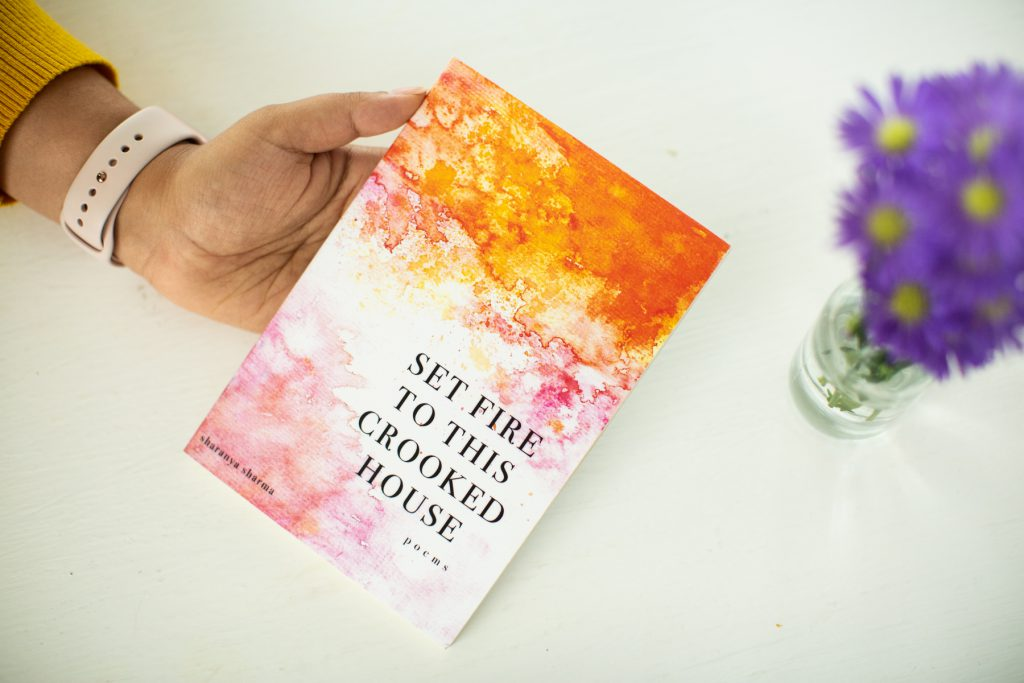 "Image: A copy of Sharanya Sharma's MFA thesis, a poetry collection entitled ""Set Fire to This Crooked House."" From off-camera, Sharma's hand angles the thesis toward the camera. The thesis is bound with a colorful cover, on which orange and pink watercolors fade into each other and into white. The title appears in all capital letters and the words ""poems"" and ""sharanya sharma"" in all lower-case. On the white tabletop is a vase of purple and yellow flowers. Photo by Kristie Kahns Photography."