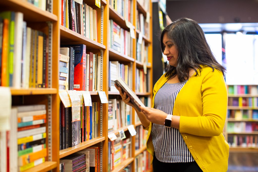 Image: Sharanya Sharma. Sharma stands inside a bookstore, oblique to the camera, looking down at a book held in both hands. Sharma wears a marigold cardigan open over a black and white striped shirt, with black pants. The bookstore is bright with daylight. A long, tall set of shelves occupies the left side of the frame. Photo by Kristie Kahns Photography.