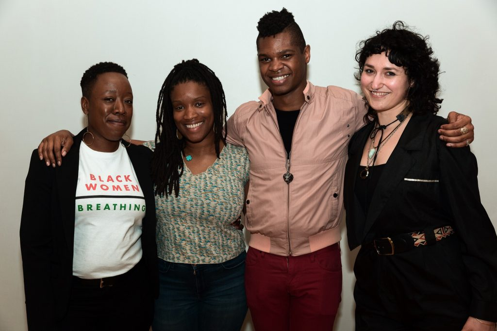 """Image: Regina Martinez with Threewalls colleagues. Dr. Jeffreen M. Hayes, Lauren Williams, Omar Dyette, and Martinez (from left to right) stand with arms around each other, posing for the camera. Hayes wears a black jacket open over a white t-shirt that reads """"Black Women 