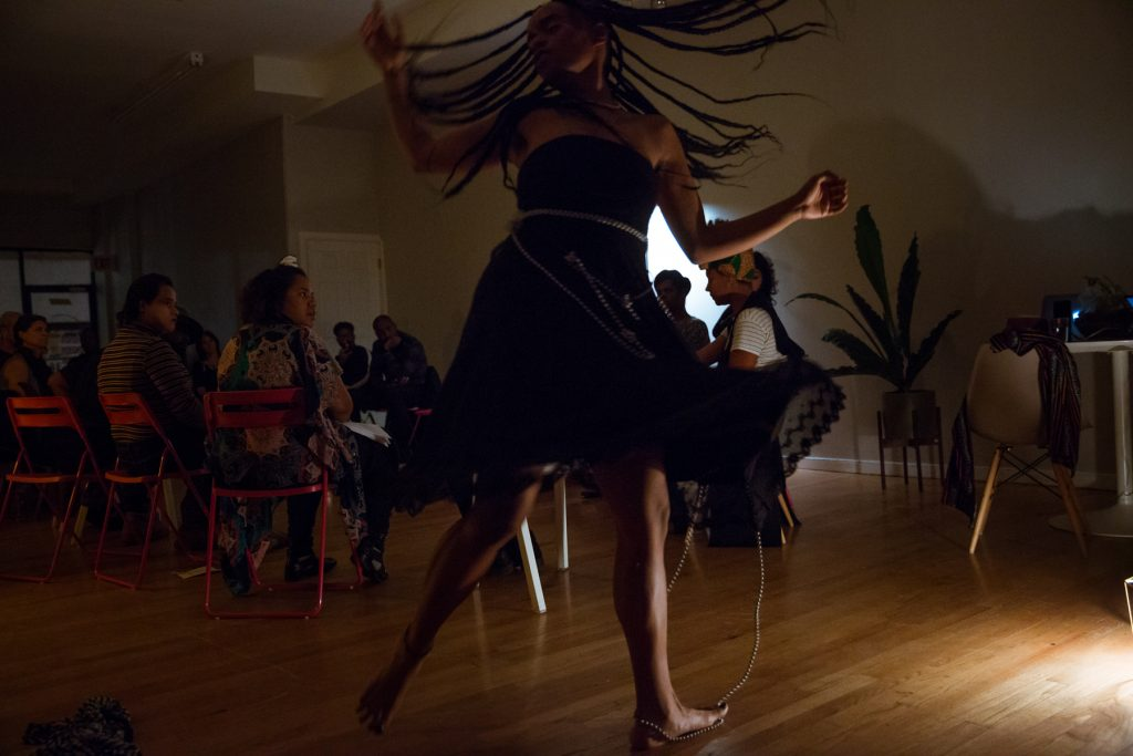 """Image: In-Session, at Threewalls in November 2018, by Najee Searcy and collaborators, in response to the guiding work """"Hush: Don't Say Anything to God: Passionate Poems of Rumi"""" by Shahram Shiva. Ester Alegria of Zo//Ra performs in the foreground. Alegria is in mid-motion, as if spinning or twisting quickly, with arms out and one foot off the ground, and long braids and the bottom of a black dress flying outwards. The artist wears a black strapless dress, with a length of silver beads tied around its bodice and extending onto the ground, under and around the performer's left foot. In the background of the dim room, audience members sit in a circle, most of them turned toward the performer. Photo by Milo Bosh. Courtesy of Threewalls."""