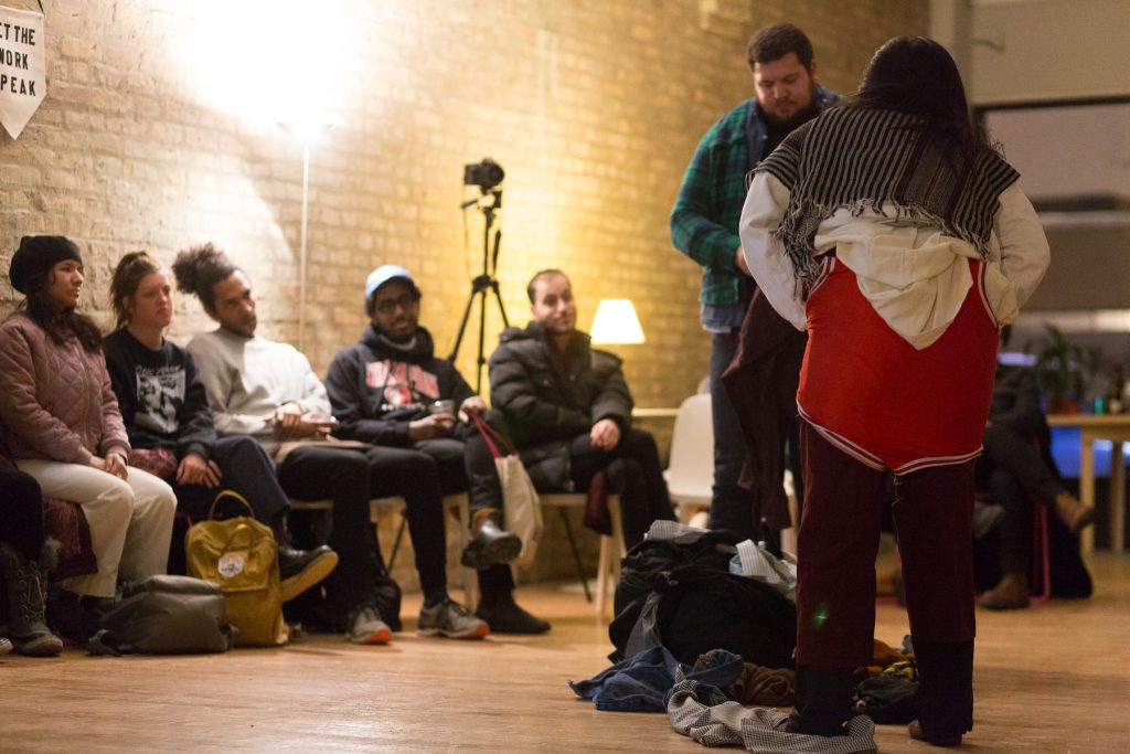 """Image: In-Session, at Threewalls in February 2018, by Jose Luis Benavides and collaborators, in response to the guiding work """"Mexican American Disambiguation"""" by José Olivarez. In the foreground, two performers stand, one facing the camera and one facing away from it, each wearing layers of varied clothes, including pants of varying lengths, multiple button-up shirts, and what appears to be a wrestling uniform. On the floor between them is a pile of still more clothes. In the background, several audience members watch from their chairs. Some audience members wear coats and other cold-weather clothes. Photo by Milo Bosh. Courtesy of Threewalls."""