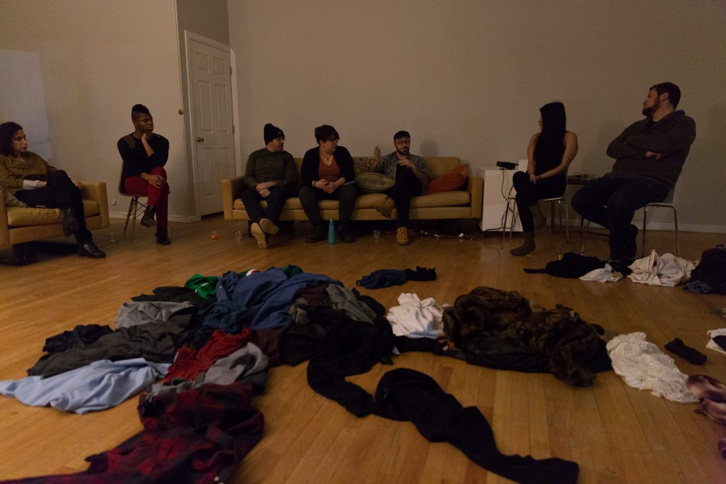 """Image: In-Session, at Threewalls in February 2018, by Jose Luis Benavides and collaborators, in response to the guiding work """"Mexican American Disambiguation"""" by José Olivarez. In the background, seven people sit on chairs or a tan couch, all looking towards the center, at Benavides, who is speaking. In the center of the low-lit room — in the foreground and around the image — is a sprawling pile of clothes. Photo by Milo Bosh. Courtesy of Threewalls."""
