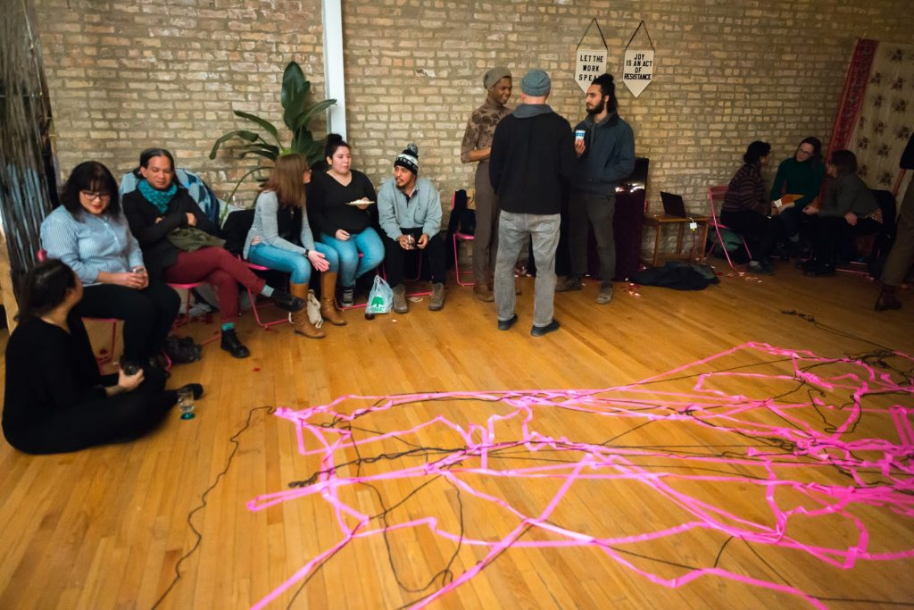 """Image: In-Session, at Threewalls in March 2019, by Maya Mackrandilal with collaborators Udita Upadhyaya and Enid Muñoz and original performance for video by Bhanu Kapil, in response to the guiding work """"Schizophrene"""" by Bhanu Kapil. In the background of this shot, trios of audience members and performers sit or stand around the room, chatting after the performance and discussion. Remnants of the performance are in the foreground — a layered web of pink fluorescent ribbon and black string on the wood floor, reflecting where many audience members stood during one part of the performance. Many audience members wear hats, sweaters, or other cold-weather clothes. Photo by Milo Bosh. Courtesy of Threewalls."""