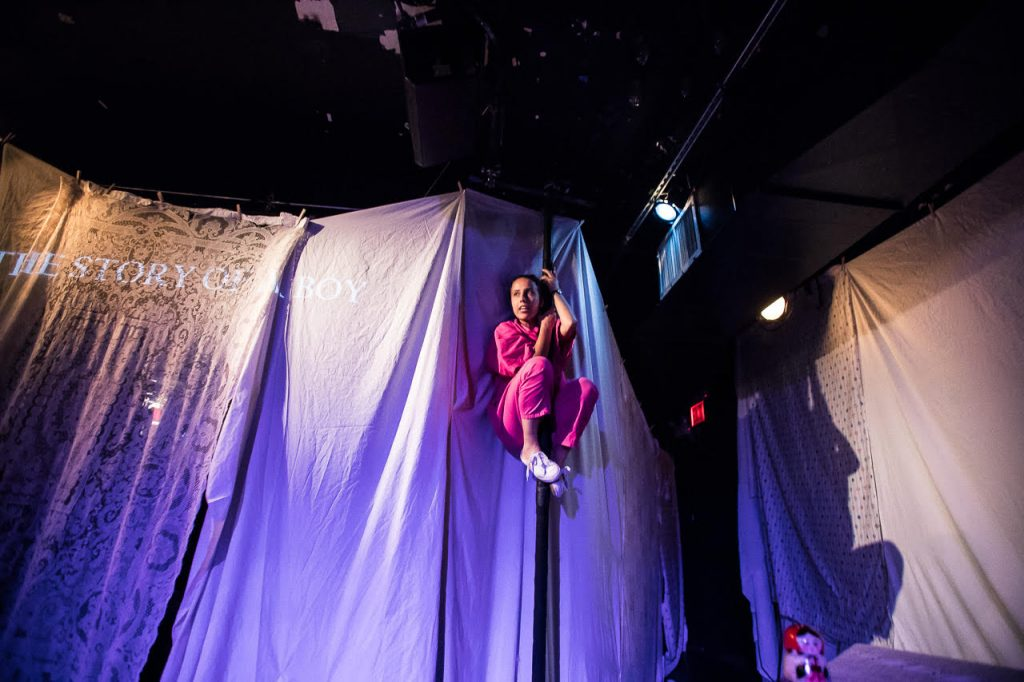 "Image: Center, Ida holding herself in a crouch position on a pole in front of a wall of curtains. To the left at level with Ida's head, projected across a taffeta sheet and a bedsheet are the words ""THE STORY OF A BOY."" To the right, the sheets taper off into a hall and at the top, a red exit sign. Further right, Ida's shadow on the wall. Below that on top of a box, a Russian nesting doll. Photo Courtesy of Brave Lux, Inc."