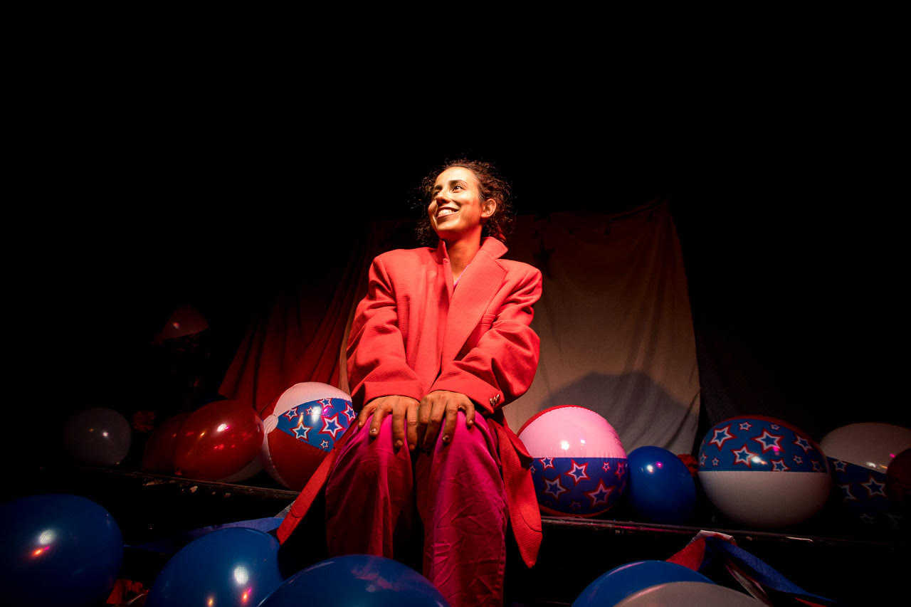 Image: Ida Cuttler, wearing a red blazer over pink pajamas, sits with her hands on her knees center. On the ground around her, are red and blue balloons and red-white-and-blue beachballs. The beachballs have stars on the blue stripes. Photo courtesy of Brave Lux, Inc.