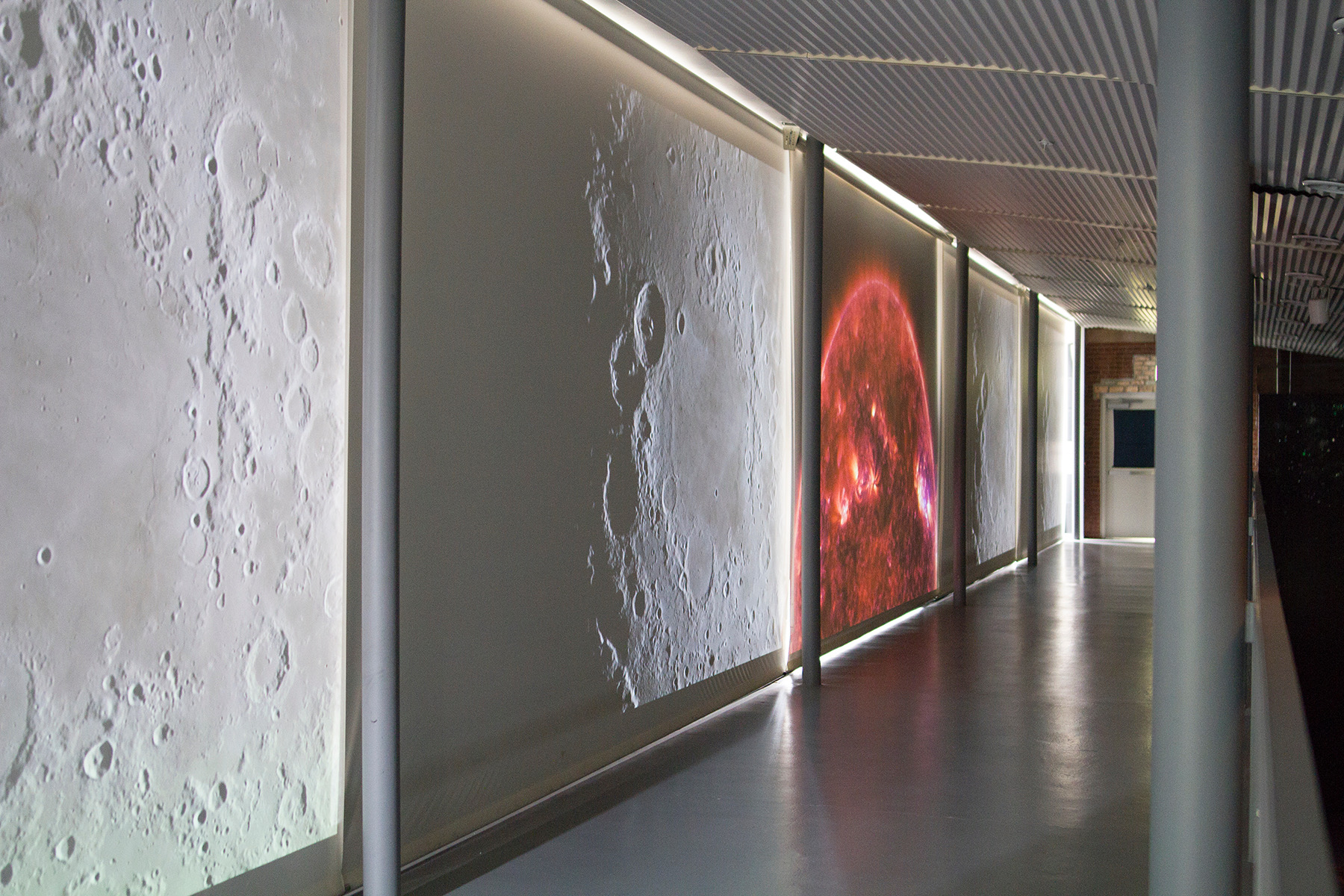 "Image: Installation view of ""Dark Matter: Celestial Objects as Messengers of Love in These Troubled Times"" by Folayemi Wilson. Catwalk with rotating NASA videos of the sun and moon. Photo by Michael Sullivan."