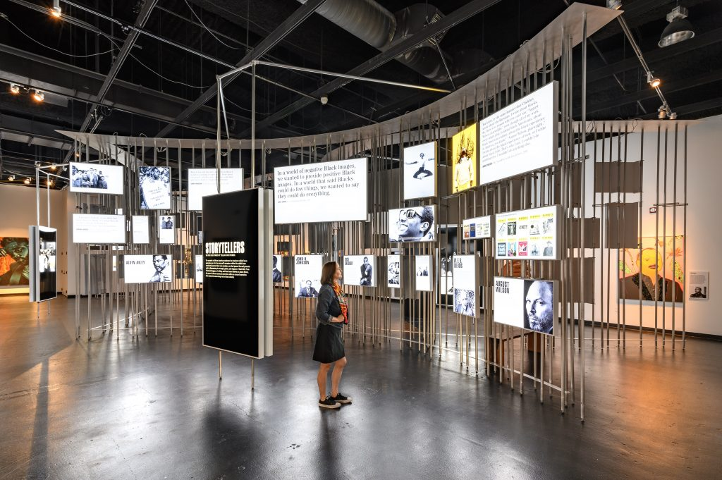 Image: Installation view of Men of Change. The installation made of metal poles is in the middle of the room. Light boxes of various sizes featuring photos and text are hung on the metal poles. A large display box in front of the installation features a poster that reads STORYTELLERS. Along the walls of the room are paintings and other artworks, most of which are obscured by the metal pole installation in the middle of the room. A woman stands in front of the light box installation, looking at the installation. Photo by Phil Armstrong. Photo courtesy of the Smithsonian Institution Traveling Exhibition Service.