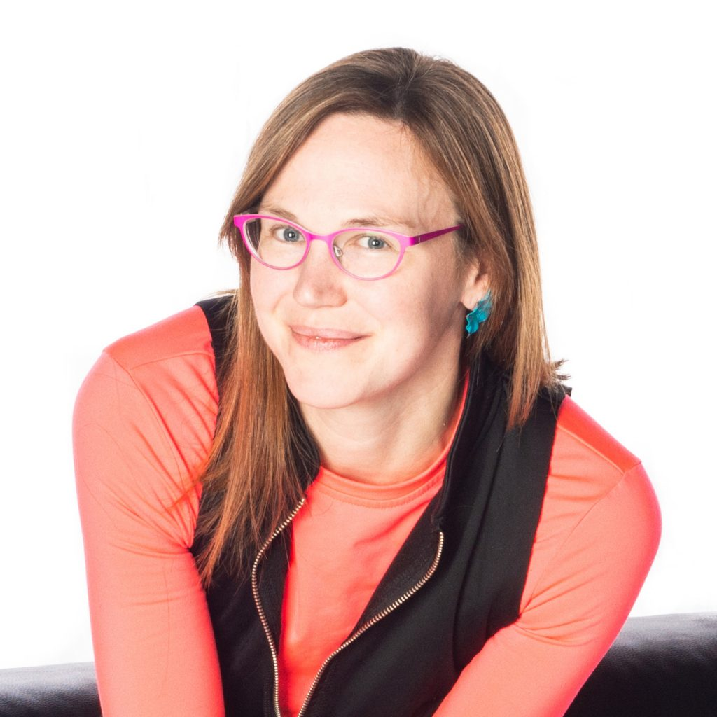 Image: A photo of Marya Spont-Lemus, shown from the chest up and smiling slightly. Spont-Lemus, a white woman, wears a black shirt open over a salmon pink long-sleeved shirt, as well as pink glasses and teal earrings. She sits on a black couch against a white background. Photo by Lucas Anti.