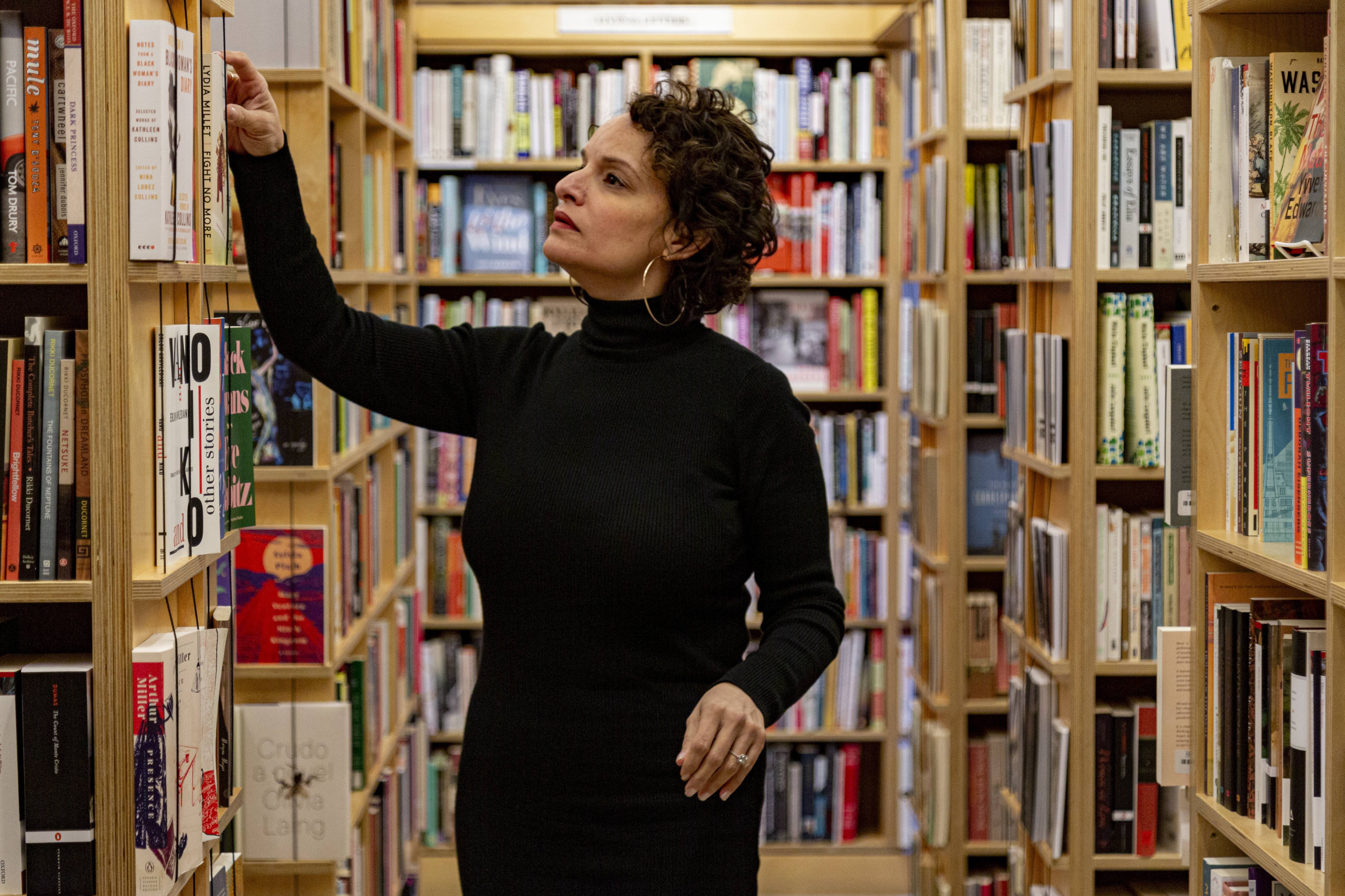 Image: Mustafah stands inside a bookstore, reaching up to pull a book off a shelf. She wears a long-sleeved black turtleneck dress and large hoop earrings. Bookshelves full of books fill the space behind and around her. Photo by Mark Blanchard.