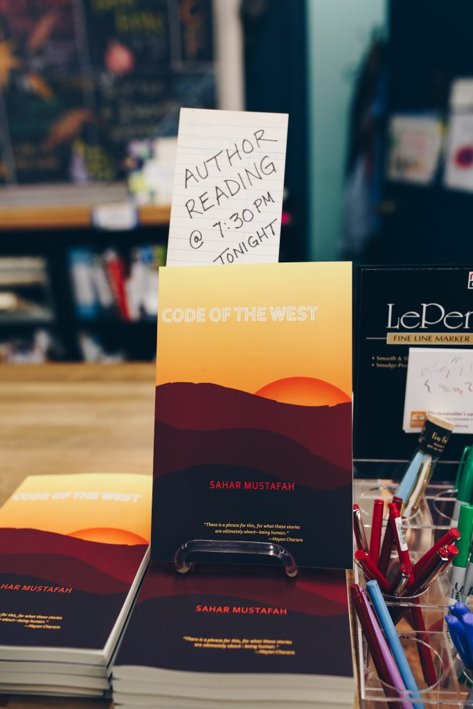 """Image: Mustafah's short story collection, """"Code of the West"""" (Willow Books, 2017). One copy of the book is displayed upright atop several other copies, which lay flat on a bookstore countertop. A hand-written paper reads, """"Author reading @ 7:30pm tonight,"""" in all capital letters. The book cover's illustration shows a sliver of orange sun behind reddish and dark brown hills, with a yellow sky above. Photo by Michelle Strahan."""
