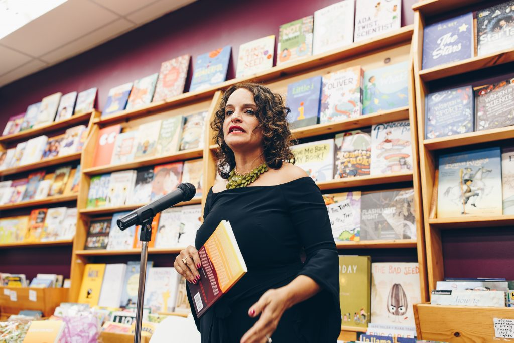 """Image: Mustafah reading at the book launch event for her short story collection, """"Code of the West,"""" at Women & Children First Bookstore in 2017. Mustafah stands, speaking into a microphone, a wall of picture books behind her. In her hand, she holds a copy of """"Code of the West."""" Mustafah wears a dramatic green necklace and an off-the-shoulder black shirt with three-quarter-length sleeves that drape open at the hem. Photo by Michelle Strahan."""