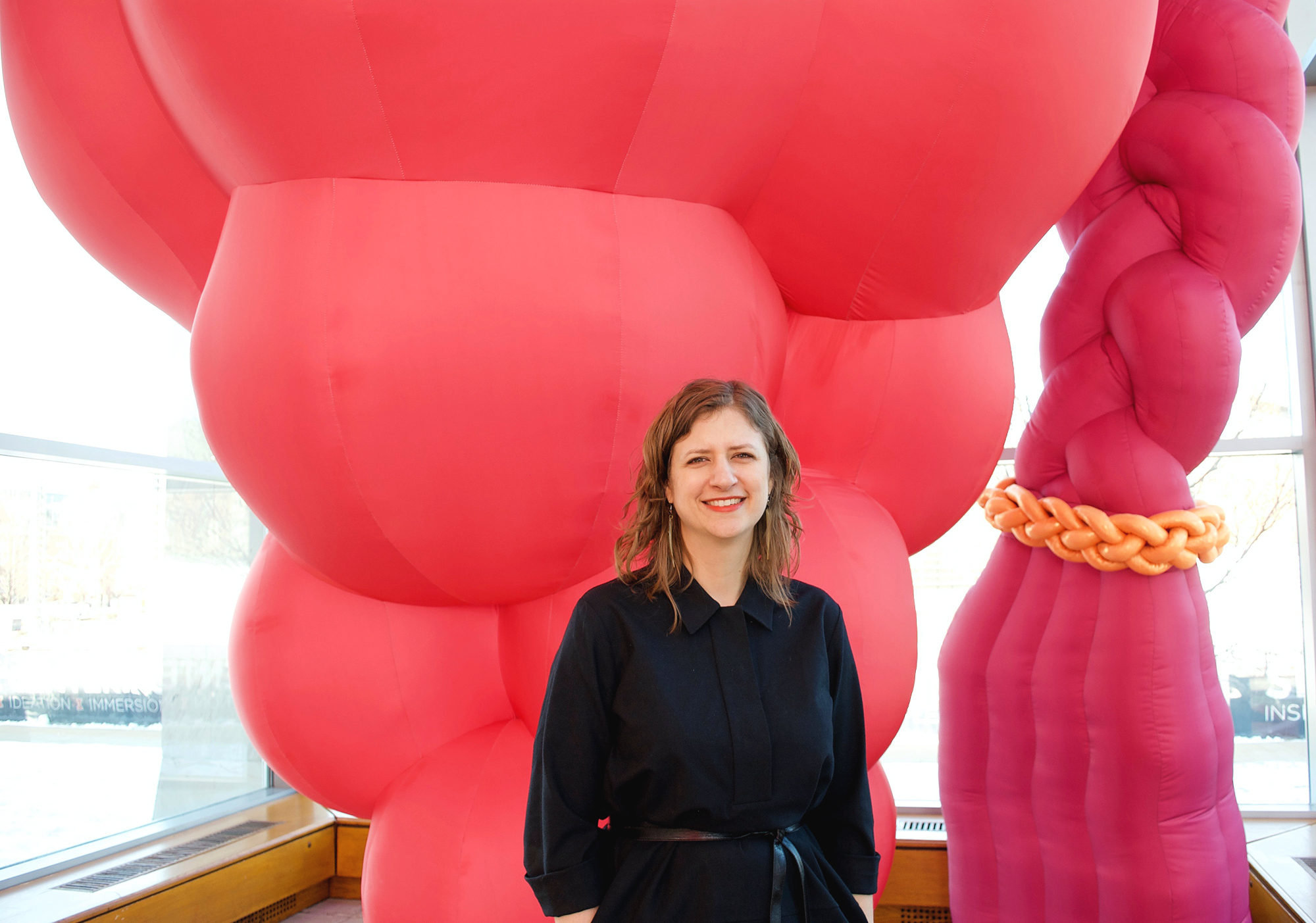 "Featured Image: Amy L. Powell, Curator of Modern and Contemporary Art at Krannert Art Museum stands in front of ""Hive,"" an large inflatable sculpture installed in the museum's Kinkaid Pavillion. The sculpture is floor to ceiling and bright pink. The main body of the sculpture resembles a bunch of grapes, or a multi-breasted female body, and to the side there is fuschia colored a braid with a braided gold band around the end of the braid. Powell stands in the center of the image, looking into the camera and smiling. She is wearing a black dress, and her hands are in her pockets. Photo by Jessica Hammie."
