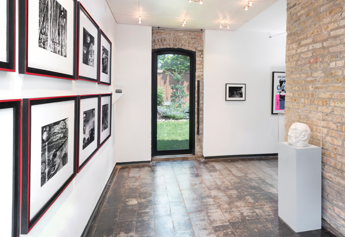 """Image: Installation shot of Iceberg Projects exhibition """"David Wojnarowicz: Flesh of My Flesh,"""" June 23 – August 5, 2018. On the left wall, a series of images are hung in rows. A sculpture of a head is encased in glass on the right way. Directly in front of the viewer, an outdoor green space is visible through a glass door. Image courtesy of Iceberg Projects."""