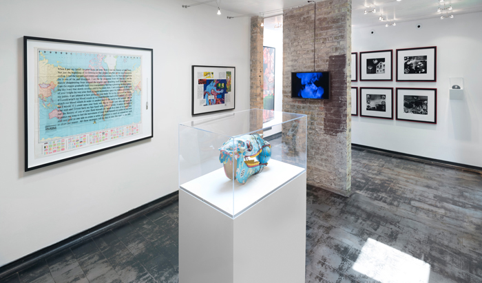 """Image: Installation shot of Iceberg Projects exhibition """"David Wojnarowicz: Flesh of My Flesh,"""" June 23 – August 5, 2018. In the middle of the room, a sculpture sits on a white pedestal, encased in glass. A world map with words overlaying the image is hanging on the wall to the left, and a video screen is displaying a video on the partial brick wall directly in front of the viewer. Image courtesy of Iceberg Projects."""
