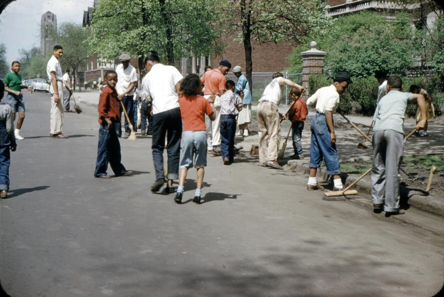 University of Chicago Photographic Archive, [apf2-09786], Special Collections Research Center, University of Chicago Library. Photo shows about a dozen adults and children outdoors in Chicago's Hyde Park-Kenwood neighborhood, many of them sweeping the streets with brooms.