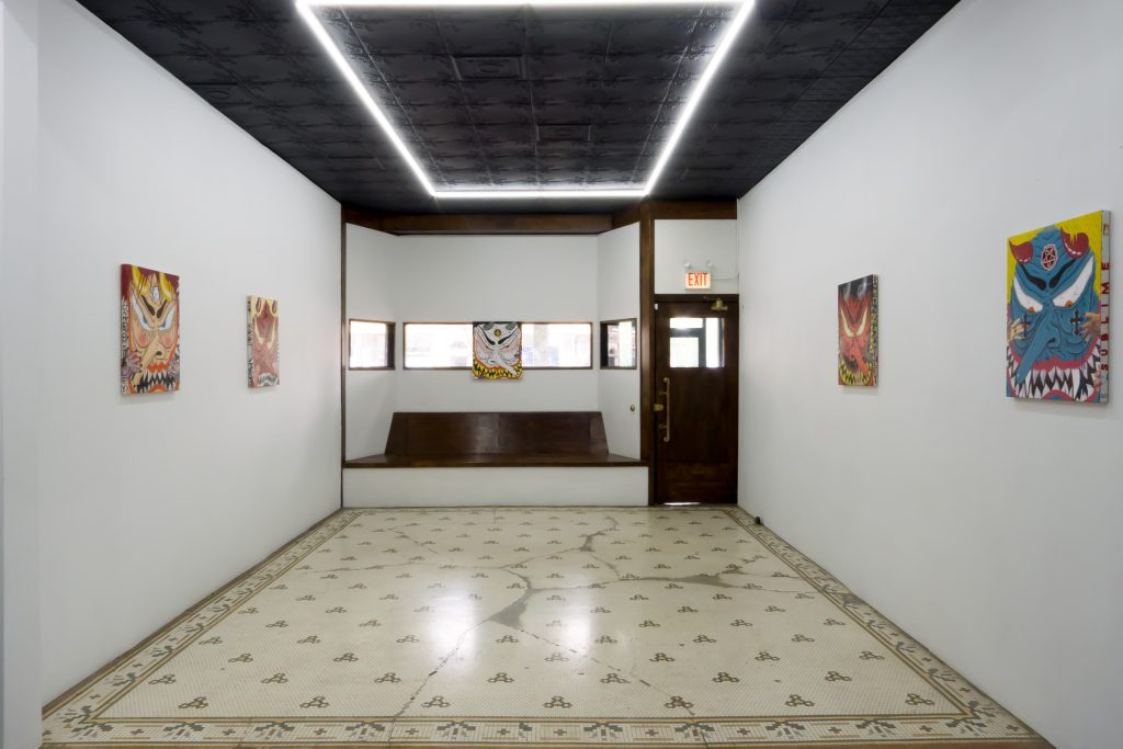 Image: An installation view of Cameron Spratley's exhibition 740 at M. LeBlanc. The image shows a view looking of the gallery space looking straight back towards the front door. Paintings from Spratley's series Devils hang on the wall. Image courtesy of M. LeBlanc.