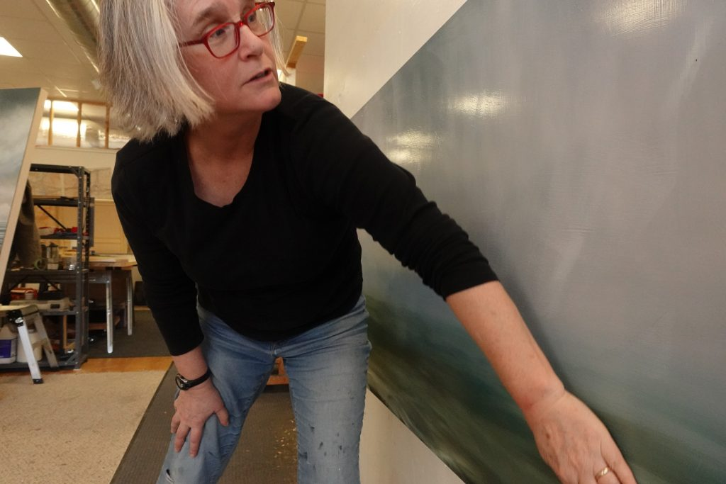 Image: The artist is leaning slightly forward wearing a black long-sleeved shirt and blue jeans. She is tilting her head towards the right of the photo with her hand working on a painting. Photo by David Travis.