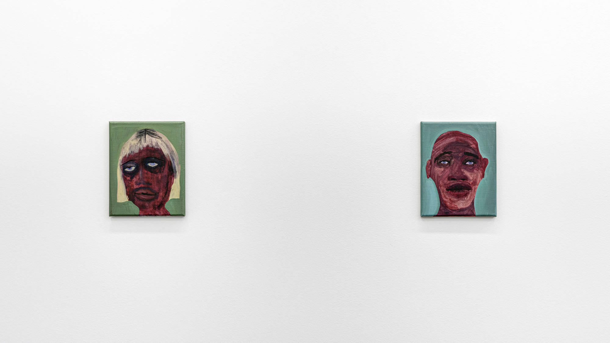 Image: Work by February James. We Laugh Loud So The Spirits Can Hear, 2020. Installation view. Two small scale oil-painted portraits hang on a wall. The dark-skinned faces are depicted in a washy style, which creates a stark contrast to the flat backgrounds of sage green (left) and turquoise (right). Image courtesy of the artist and Monique Meloche Gallery.