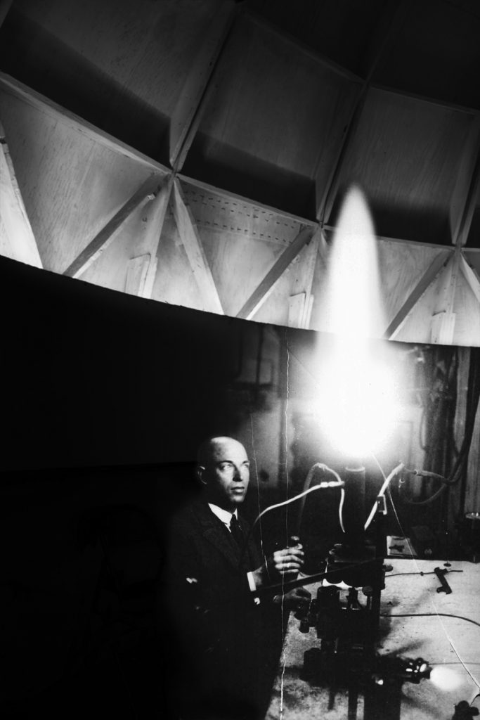 Image: Fuel Test, Peenemünde, 1939/2019 by Barbara Diener. A black and white photograph of a man conducting a fuel test. A bright light from the test is on the right side of the photo, with the left half dominated by darkness. Image courtesy of the artist.
