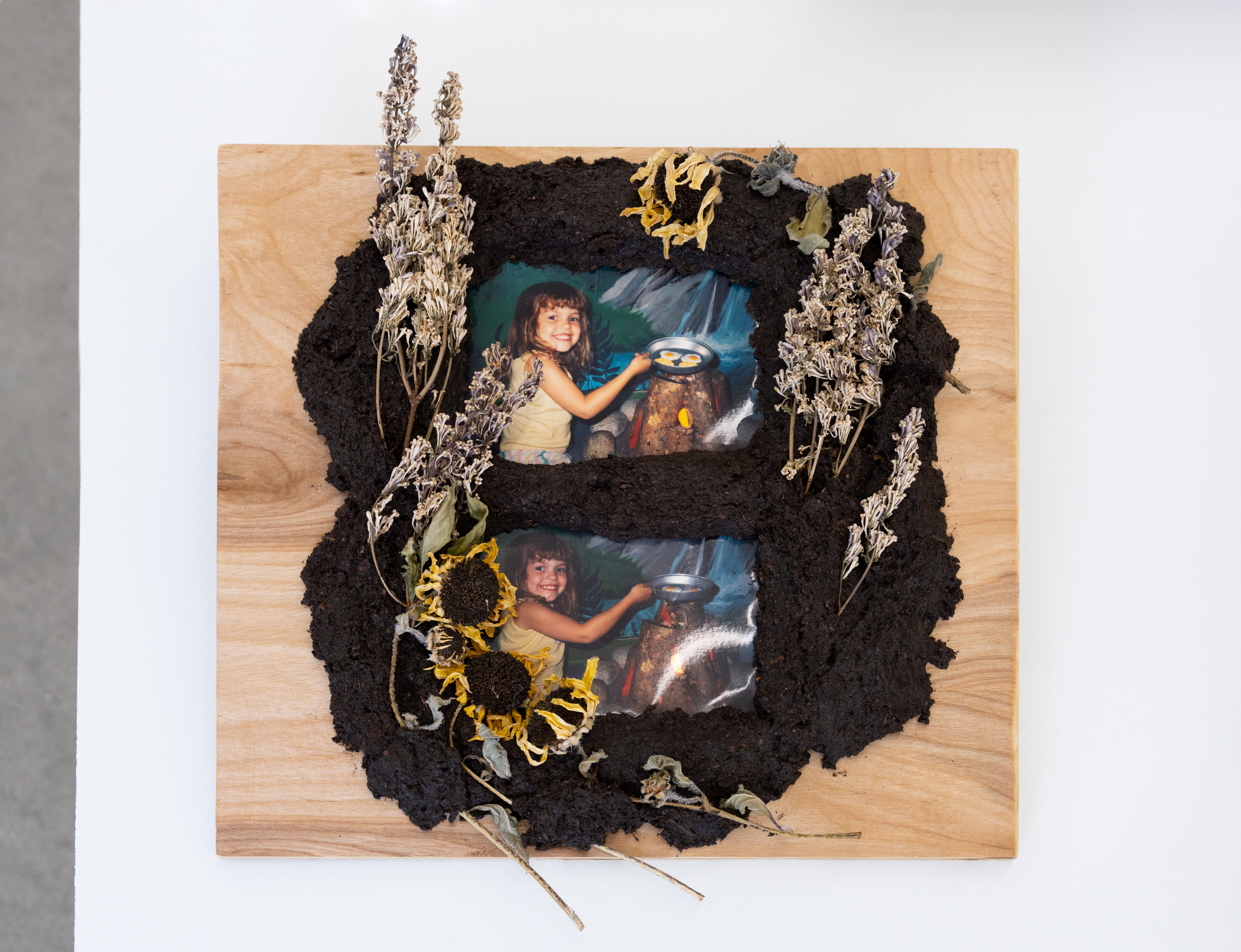 """Image: Lilacs, 2020 by Cass Davis. Cast soil, wooden panel, photographs, resined lilacs, and sunflowers, 13 x 12"""". Two photographs of a young girl sits under soil, lilacs, and sunflowers on wood. Image courtesy of the artist. Photo by Nick Albertson."""