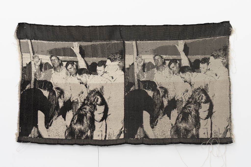 """Image: Revival II, 2016 by Cass Davis. Jacquard woven cloth, 13 x 28"""". The cloth has two near identical images of a revival scene in black and white. The scenes show a crowd of people with their hands in the air. The piece hangs on a white wall. Image courtesy of the artist. Photo by Nick Albertson."""