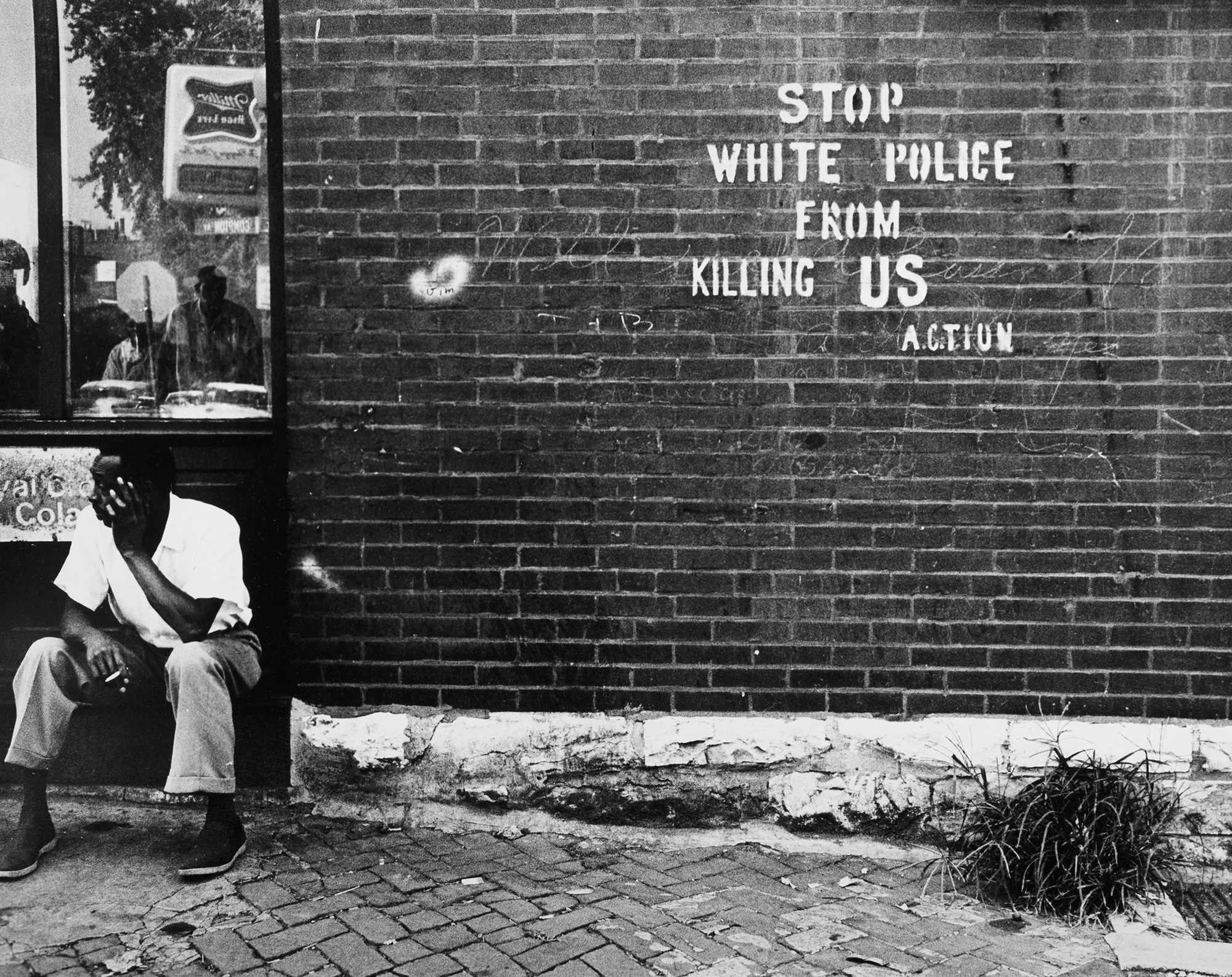A black and white photograph titled Stop White People From Killing Us - St. Louis, MO, c. 1966-67 by Darryl Cowherd