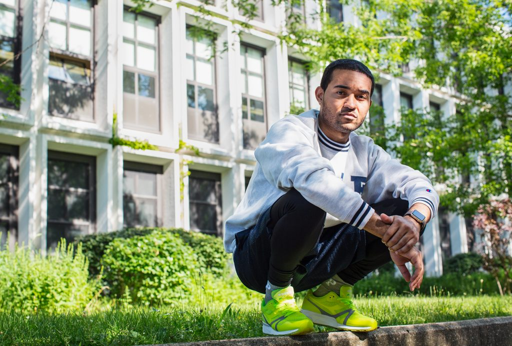 Image: Kristoffer McAfee in front of Kenwood Academy High School, a place where he says his interest in art was nurtured, and he emerged as a painter. McAfee is wearing a white sweatshirt, black pants, and neon yellow sneakers while squatting on a concrete ledge. He is looking directly at the viewer.  Photo by Kristie Kahns.