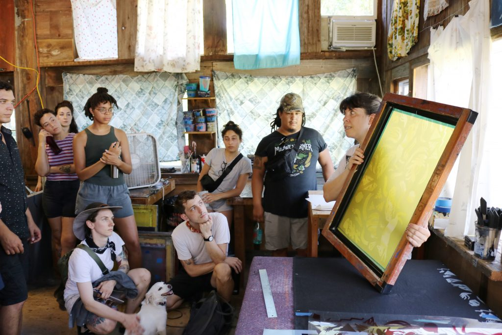 Image: As part of ACRE's residency program, artists are sitting and standing while watching a screen-printing demonstration. Photo by Zachary Hutchinson, courtesy of ACRE.