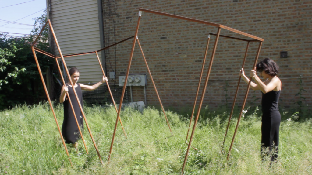 "Image: ""Join"" by Cecilia and Marina Resende Santos, an installation/performance that took place on June 6, 2020 at an empty lot for sale by Landmark Property in Bridgeport. Two people pull apart an octagon metal frame. Photo by Graham Livingston."