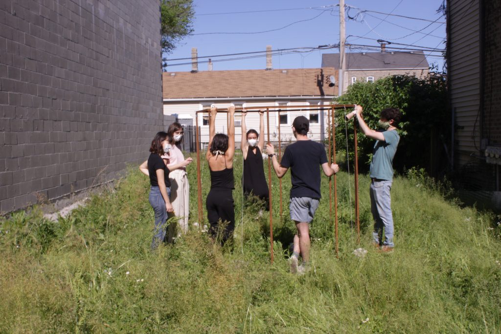 "Image: ""Join"" by Cecilia and Marina Resende Santos, an installation/performance that took place on June 6, 2020 at an empty lot for sale by Landmark Property in Bridgeport. Six people stand around an octagon metal frame. Photo by Graham Livingston."