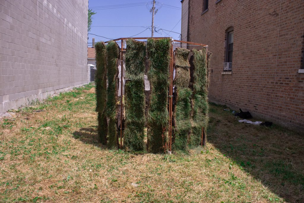 "Image: ""Molt"" by Graham Livingston, on view October 21 - November 1, 2020 in Garfield Park. An octagon metal frame with strips of dirt and grass as the walls of the structure. Photo by Marina Resende Santos."