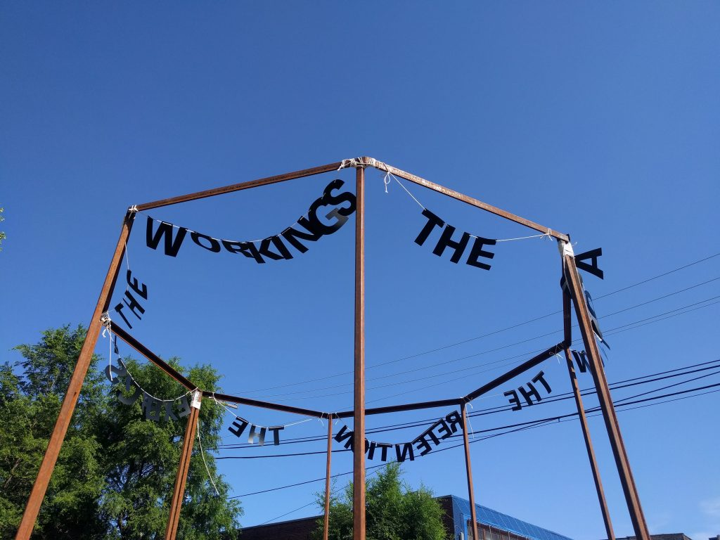 "Image: ""Untitled Politics"" by Uniymeabasi Udoh, installed on July 13, 2020 at El Paseo Community Garden on Cullerton St and Csangamon St. in East Pilsen. Letter garlands are installed across the tops of an octagon metal frame. The letters in the foreground spell ""WORKINGS"" and ""THE"". Photo by Cecilia Resende Santos."