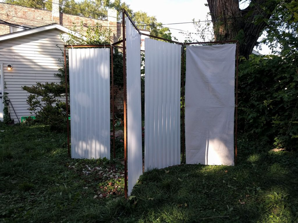 "Image: ""Avesso"" by Cecilia and Marina Resende Santos, on view at The Franklin in Garfield Park from September 30, 2020 to the end of the year. The octagon metal frame that was used for other Open Sheds installations are installed in a way that creates an open 'X' shape. White, hanging material create walls in the structure. Photo by Cecilia and Cecilia Resende Santos"