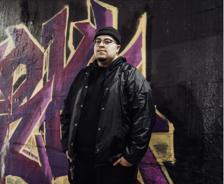 Imagen de portada: CeaseDays lleva un gorro negro, una chaqueta negra con una sudadera con capucha negra debajo y jeans negros. Tiene las manos metidas en los bolsillos del jean. Está frente de un mural de graffiti con el color del base negro y letras de color morado y amarillo.