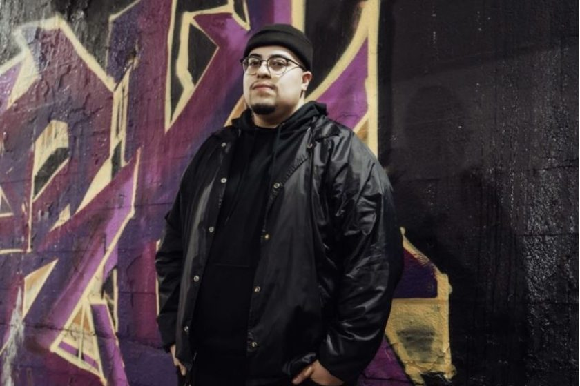 Featured Image: CeaseDays is wearing a black beanie, a black windbreaker with a black hoodie underneath, and black jeans. He has his hands tucked in his jean pockets. He is standing in front of a graffiti mural with a black background and purple and yellow letters.
