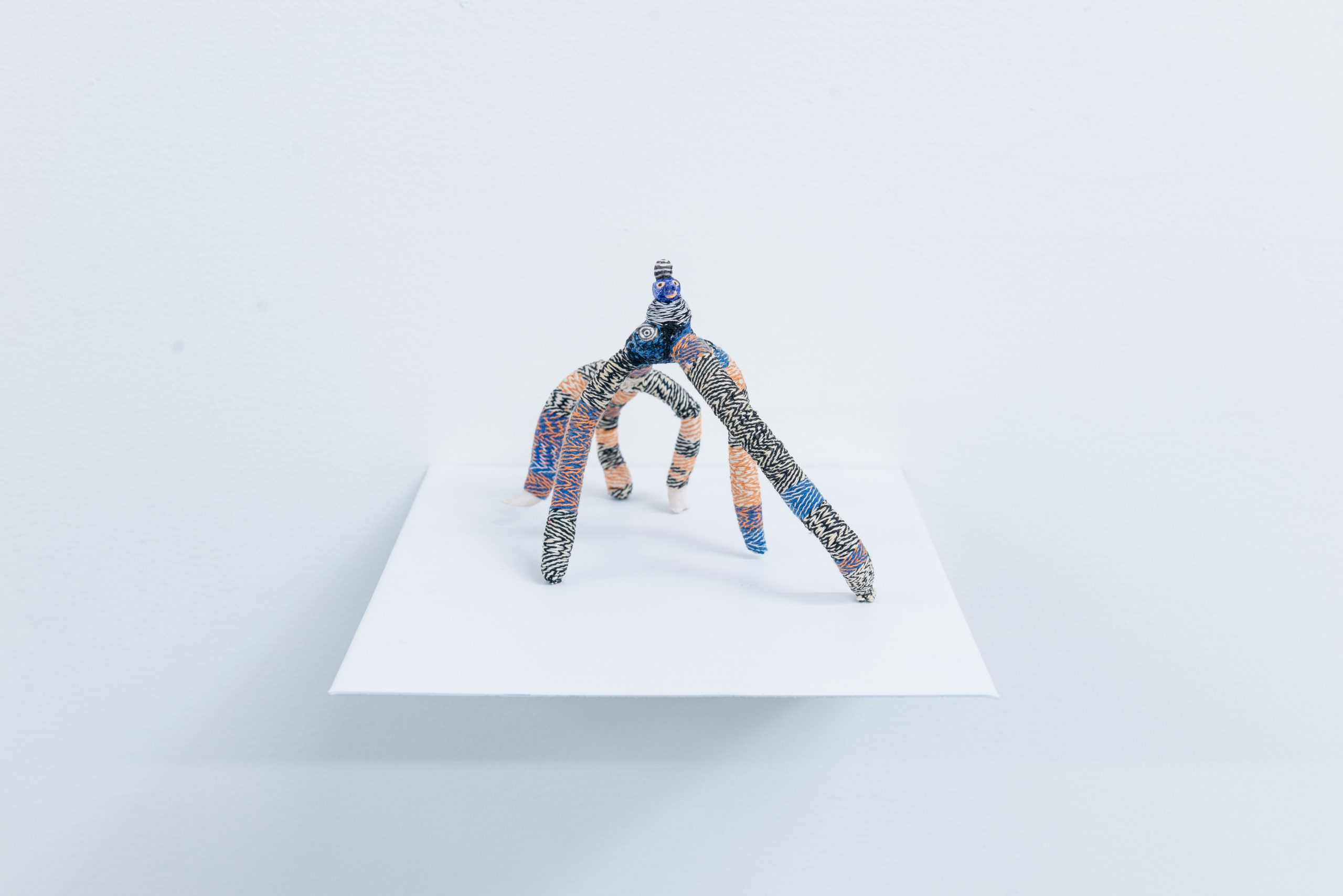 The Creep by Em Kettner; a six-legged, woven, porcelain figure looks straight ahead