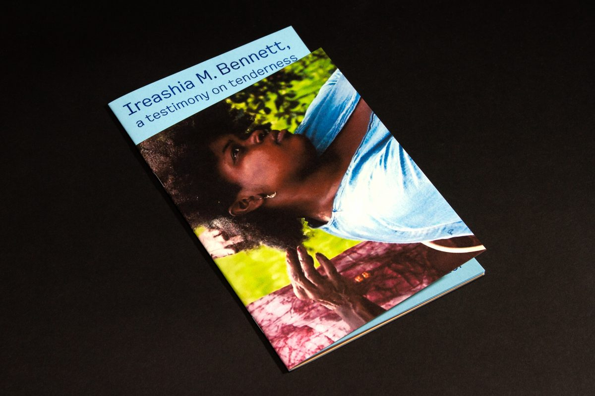 Image: A photo showing the front of the zine issue with an image by artist Ireashia M. Bennett on the cover. The booklet sits slightly open on top of a jet black background. Photo courtesy of Candor Arts.