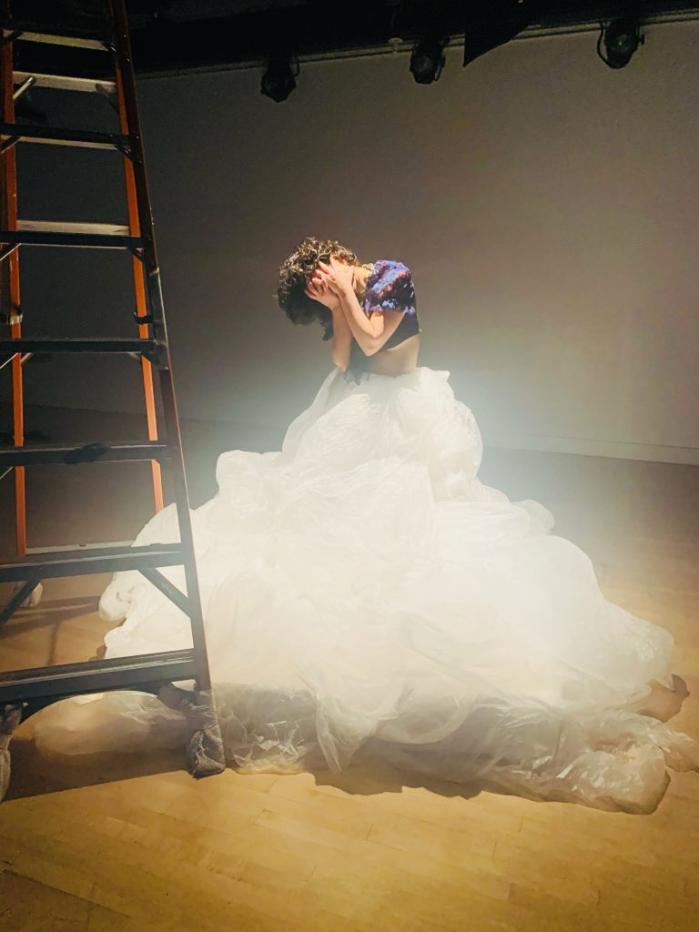 Image: A behind the scenes look at the performance Four Walls and One Me by Taimy Ramos Velázquez. A dancer stands with hands over face wearing a large white skirt.  A ladder stand to the left. Photo courtesy of the artist.