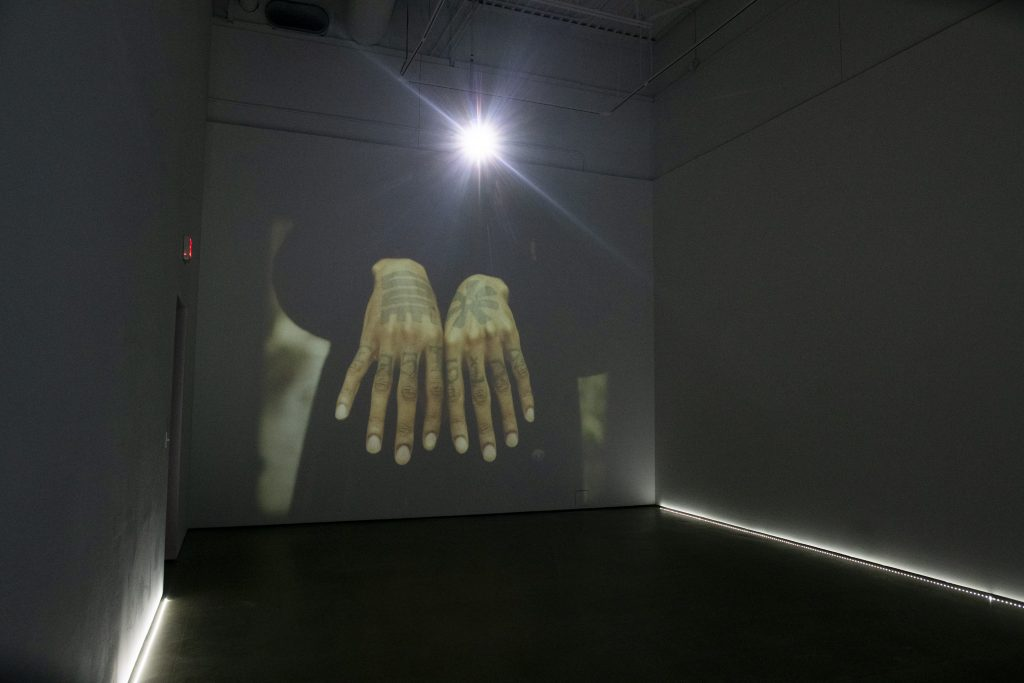 Image: Installation view of The Line by Cameron Granger. The video piece is being projected on a large wall. The still being shown is of a person holding out their hands palms down, showing tattoos on their hands. Image courtesy of the gallery. Photo by Ty Wright.