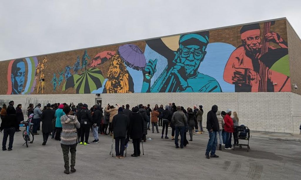 Featured image: (Mariano's mural) Color Me South Side, 2019 by Dorian Sylvain. A crowd of people stand in front of a colorful mural depicting several people. Photo by Chris Devins.