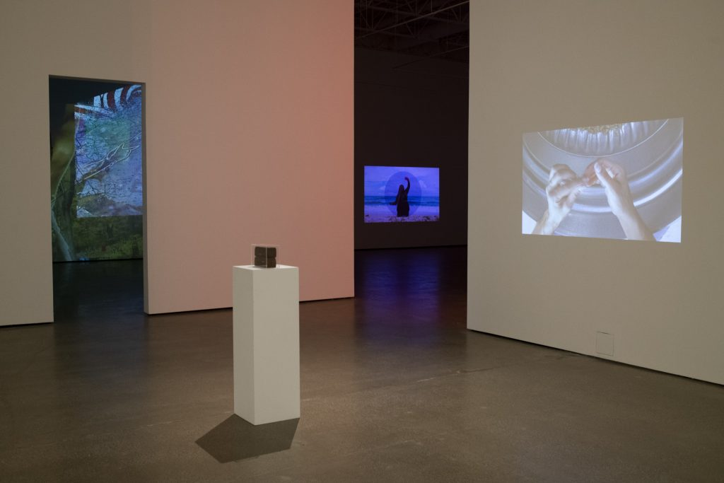 Image: Installation view of November at Beeler Gallery. The video projection on the right wall and sculpture: The Work by Lexie Smith; Drapetomania by Bobby T Luck is in the room to the left; and the video piece on the back wall: a reflection of the sky (waterway) by Adee Roberson. Image courtesy of the gallery. Photo by Ty Wright.
