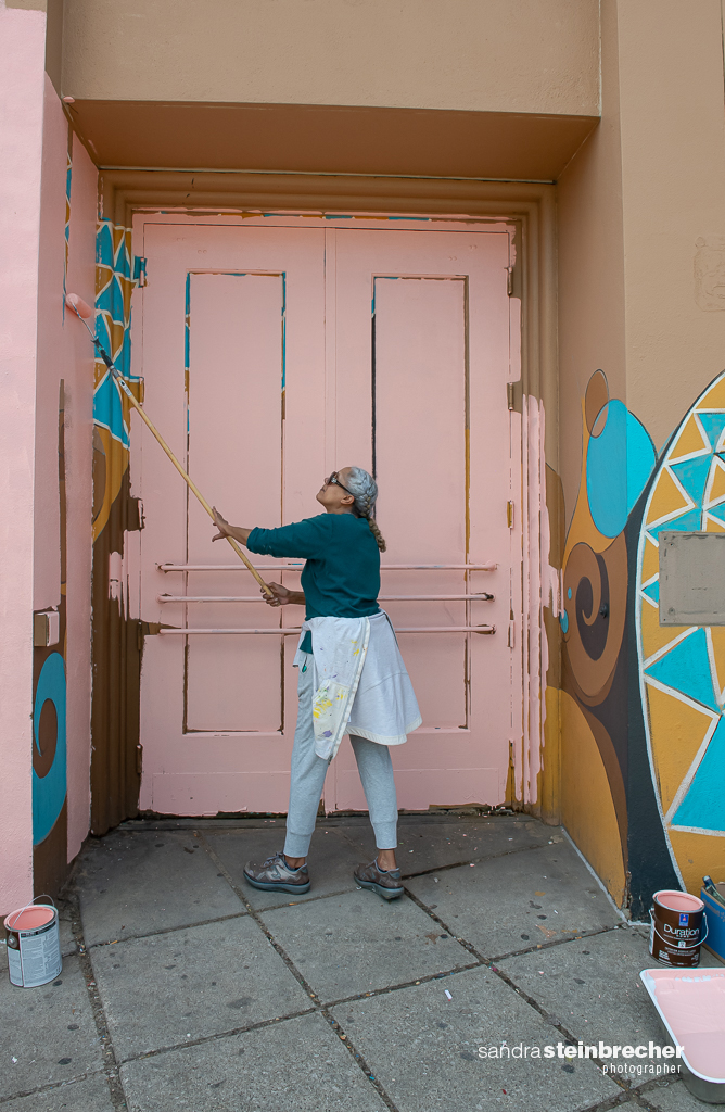 Image: Dorian working on the formerly known South Shore Bank in 2020. They stand in front of a pink wall while painting the side of a building. Photo by Sandra Steinbrecher.