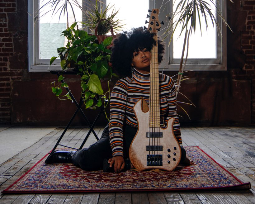 Image: A photo of Tonina Saputo sitting on a rug while posing with her guitar. Photo by Danny Zones, courtesy of the musician and the photographer.