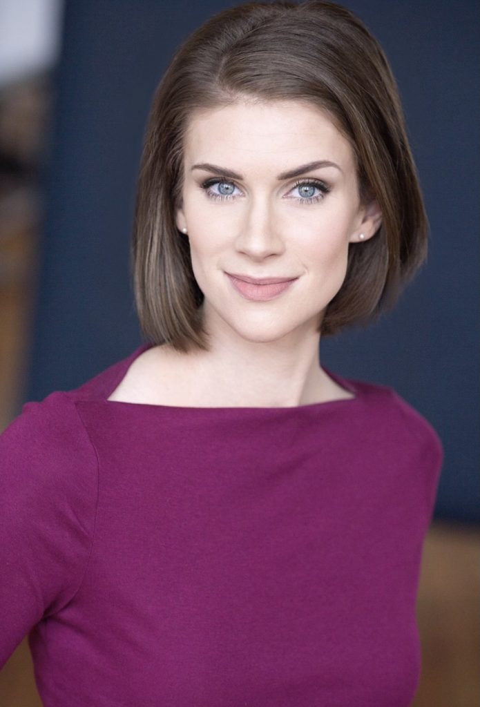 Image: A headshot of Brit Cooper Robinson. She is wearing a maroon shirt and looking straight at the viewer.