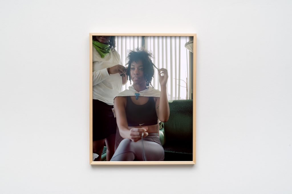 Image: Jazmine Harris, Untitled, 2020, archival pigment print. The artist is center frame, her gaze above and to the viewer's left. The artist sits at home in her grandparent's chair while she has her hair done. In her hand is a remote shutter release cable. Photo courtesy of the artist and curator.